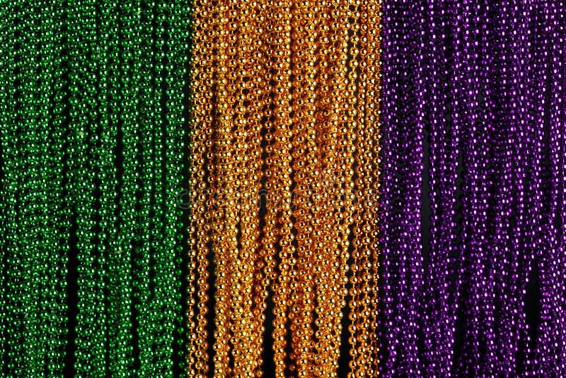 Gräsplan, guld och purpurfärgade Mardi Gras pärlor royaltyfri bild