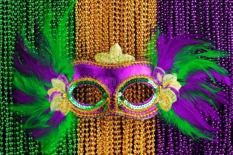Gräsplan, guld och purpurfärgade Mardi Gras pryder med pärlor med maskeringen arkivbilder