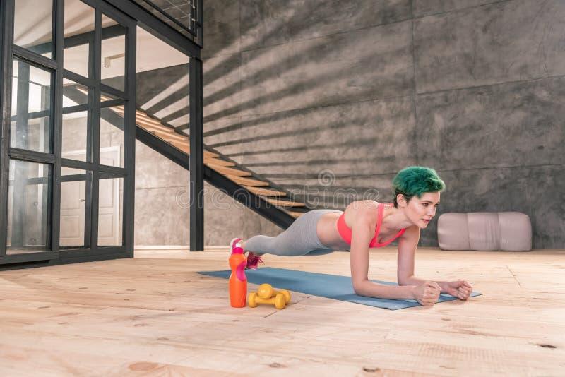 Gräsplan-haired idrottskvinna som gör morgonplankan efter genomkörare royaltyfri fotografi