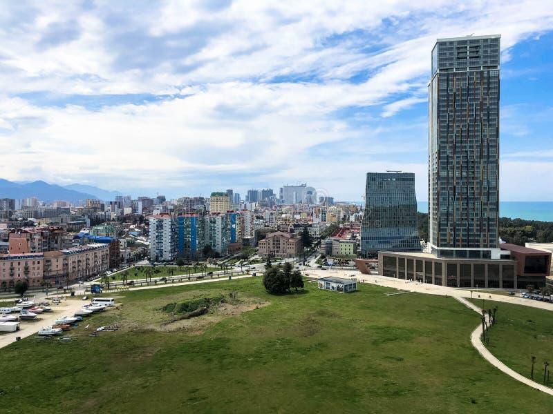 Gräsplan parkerar i en modern storstad, megalopolis med höga glashus, byggnader, skyskrapor mot den blåa himlen av bergen royaltyfri foto