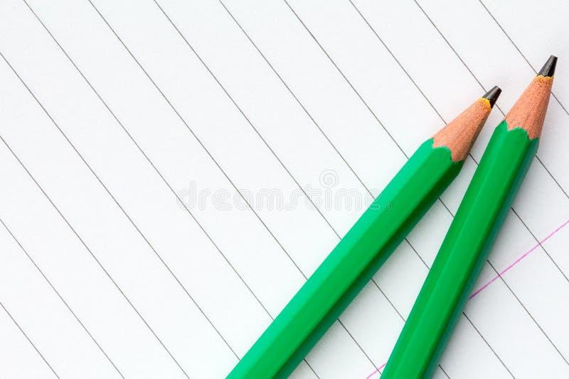 Gräsplanblyertspennor på fodrat papper arkivbild