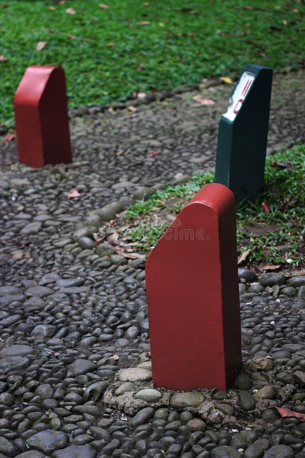 Gräsplanen och det rött undertecknar in parkera arkivfoto