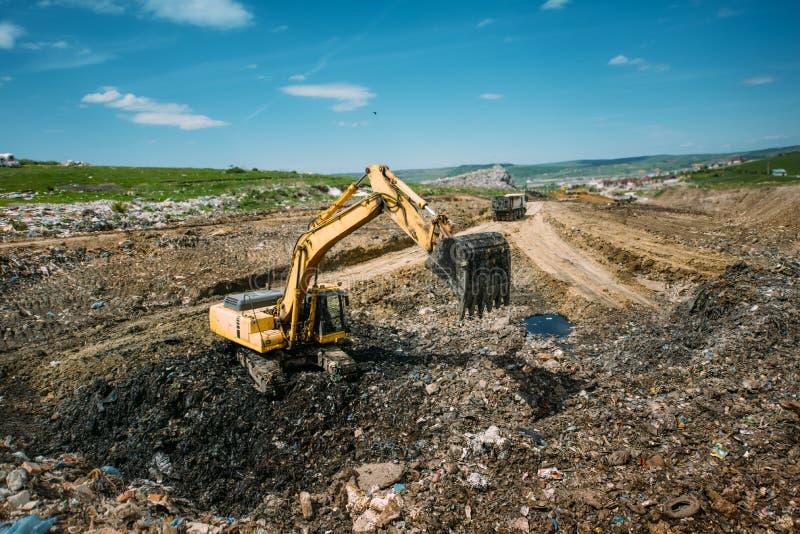 Grävskopa bulldozer som arbetar i avskrädeförrådsplats Återanvända och lösa miljöfrågor arkivfoton