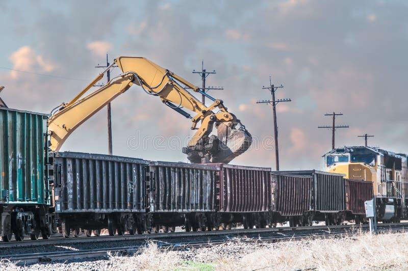 Grävskopa som laddar gamla järnvägband i öppna boxcars royaltyfria bilder