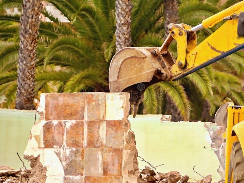 Grävskopahink som är i bruk på en väggrivning arkivbilder