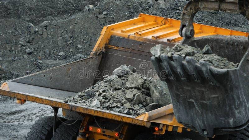 Grävskopan fyller dumper Hinkgrävskopacloseupen laddar stenar in i kropp av dumper på att bryta eller konstruktion av arkivbild