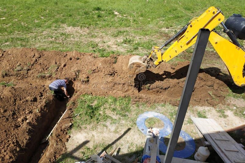 Grävskopan gräver ett dike i ett privat område för att lägga den elektriska kabeln till huset arkivfoton