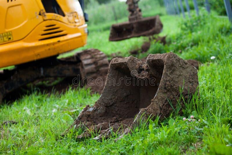 Grävskopan jämnar jorden på platsen arkivfoto
