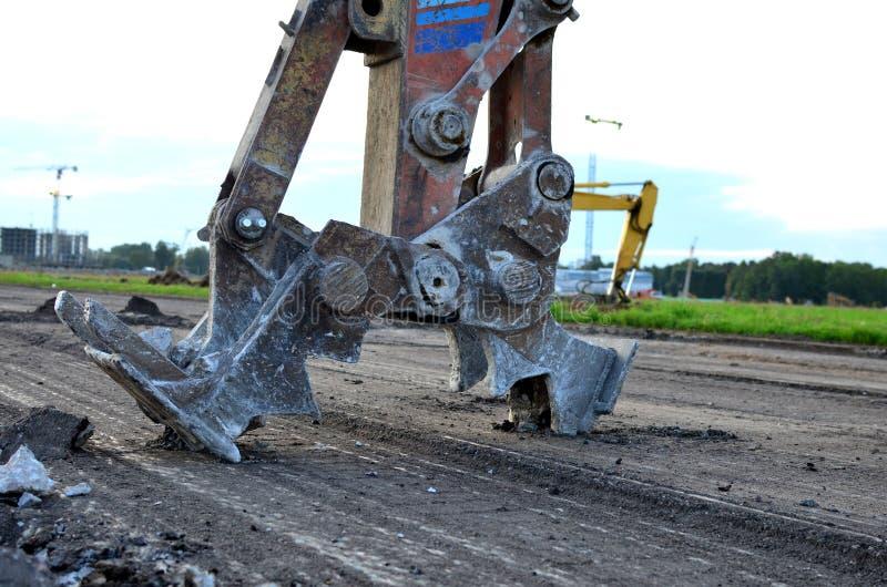 Grävskopan med hydrauliska saxavbrott asfalterar på en konstruktionsplats arkivbild