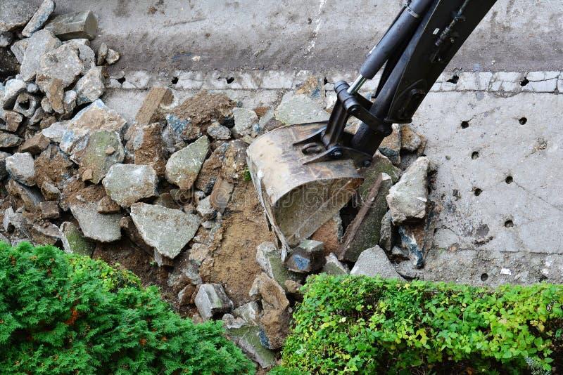 Grävskopan tar bort den gamla konkreta trottoaren Trottoarrekonstruktion fotografering för bildbyråer