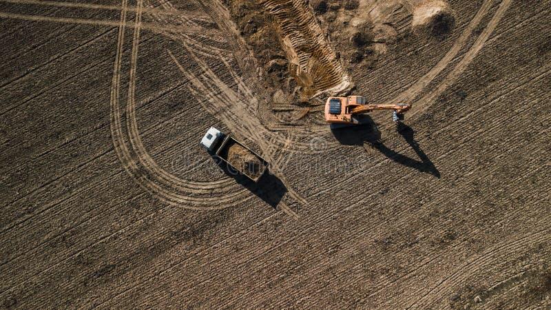 Grävskopapåfyllningar åker lastbil flyg- sikt från över med surret arkivfoton