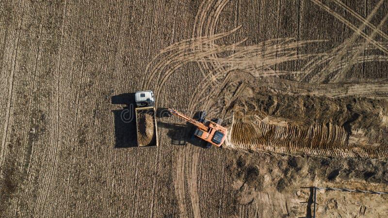 Grävskopapåfyllningar åker lastbil flyg- sikt från över med surret royaltyfri foto