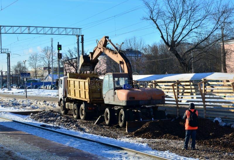 Grävskopapåfyllningar krossade stenar i en dumperkropp Konstruktion av järnvägen Förbereda yttersidan av jorden för att lägga arkivbild