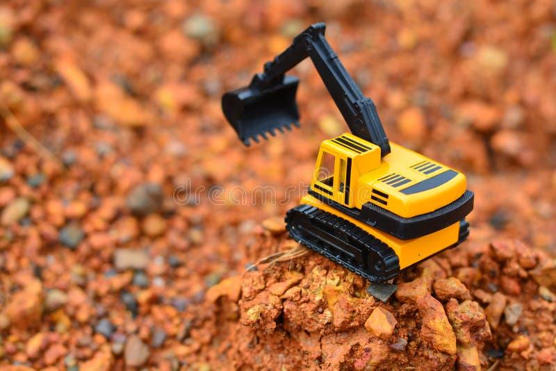 GrävskopaToy arbete på konstruktionsplatsen royaltyfri bild