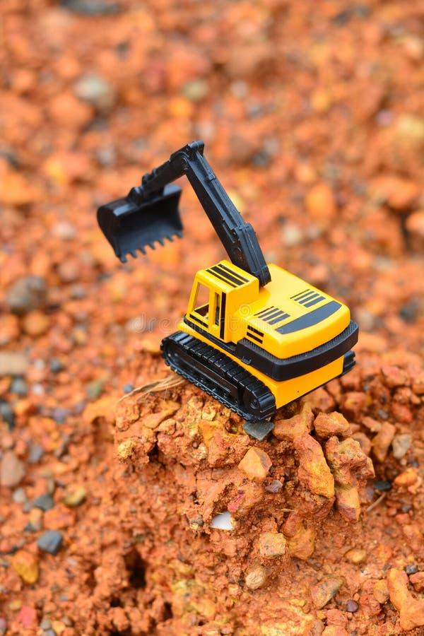 GrävskopaToy arbete på konstruktionsplatsen royaltyfria foton