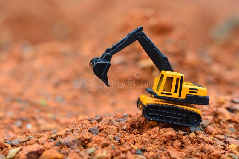 GrävskopaToy arbete på konstruktionsplatsen royaltyfria bilder