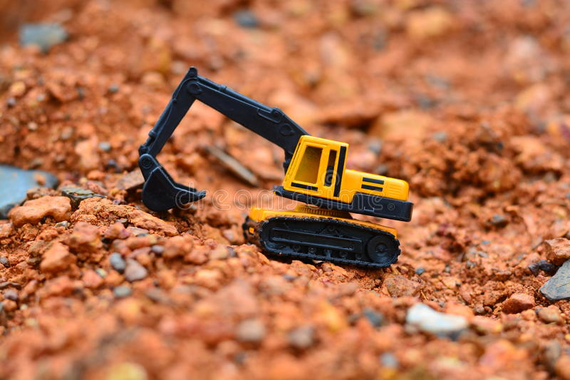 GrävskopaToy arbete på konstruktionsplatsen royaltyfri foto