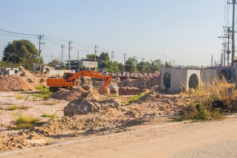 Grävskopor gräver jord för att ställa in ett stort dräneringrör nästan vägen i stadsområdet arkivbild