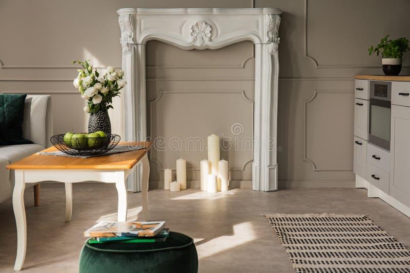 Grå öppen plankök och vardagsrum, verkligt foto med den vita spisportalen med stearinljus arkivfoto