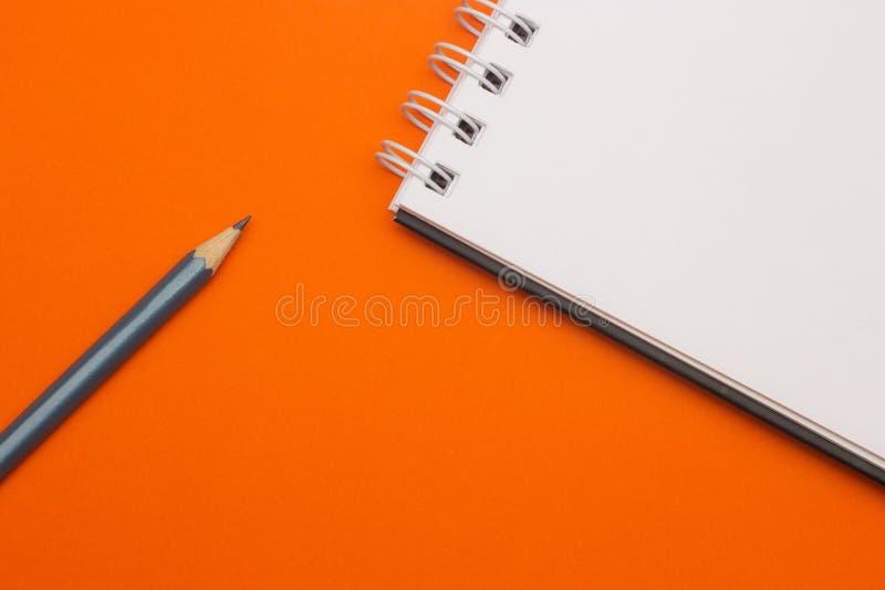 Grå blyertspenna på orange bakgrund, tillbaka till skolan, utbildningsbegrepp royaltyfria foton