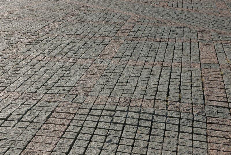 Grå brun stentextur av stenläggningtegelplattor på vägen arkivbild