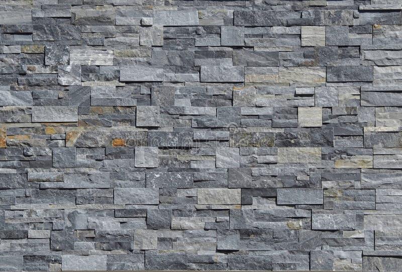 Grå cladding för stenvägg som göras av staplade remsor och fyrkantiga kvarter Bakgrund och texturerar royaltyfria bilder