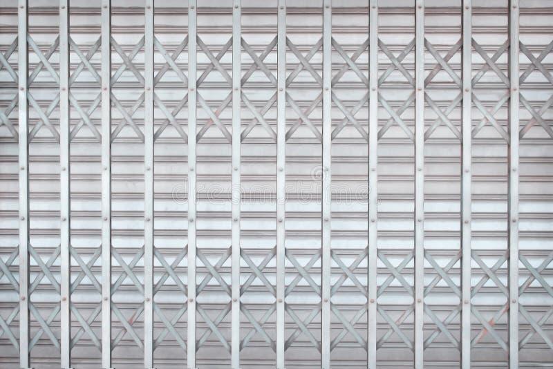Grå färg- eller silverrullningsståldörren eller rullslutaredörren i flätar samman modeller för bakgrund royaltyfri bild