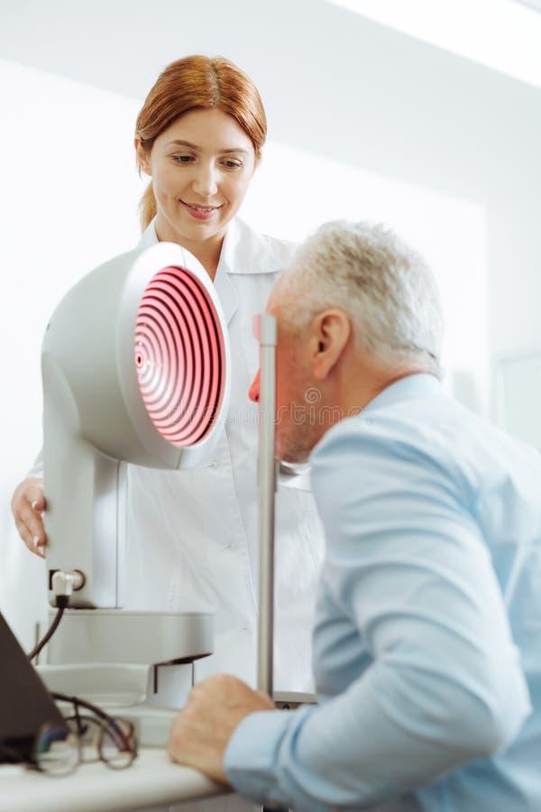 Grå färg-haired åldrig man som besöker ögonspecialisten varje år royaltyfri fotografi