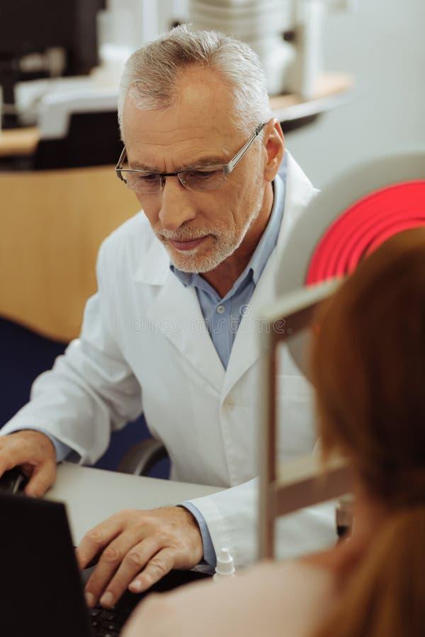 Grå färg-haired ögonspecialist som ser bärbara datorn, medan övervaka ögonsikt royaltyfri foto