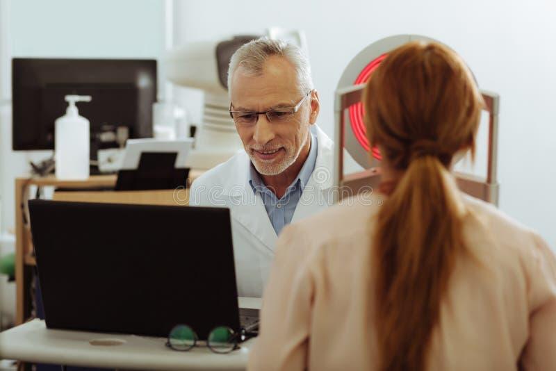 Grå färg-haired ögonterapeut som talar till hans patient arkivfoto