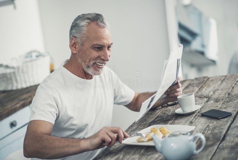 Grå färg-haired affärsman som äter läckra kräppar i morgonen royaltyfri bild