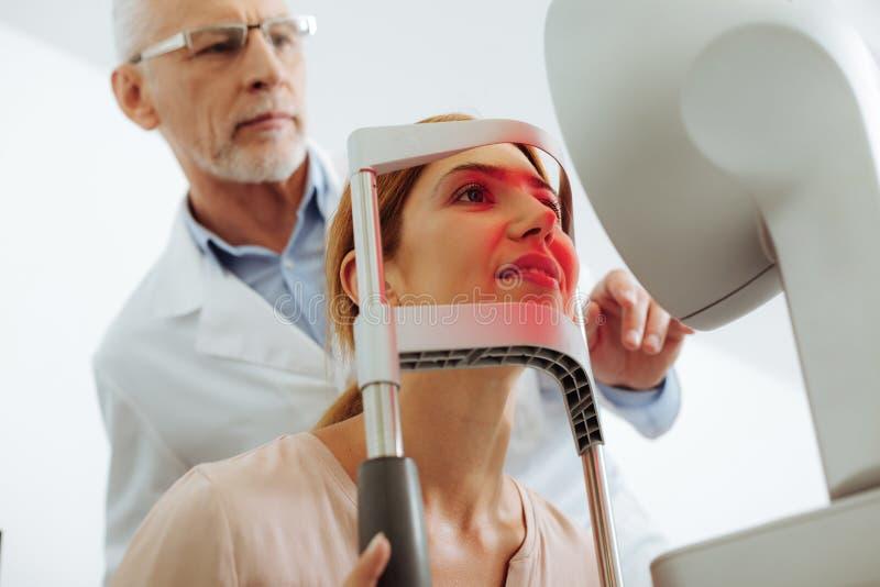 Grå färg-haired bärande exponeringsglas för ögonspecialist som konsulterar patienten arkivfoton