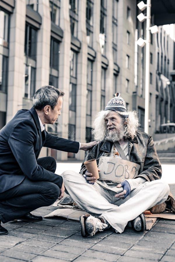 Grå färg-haired hemlös man i förstörd kläder som sitter på kall jordning arkivfoto