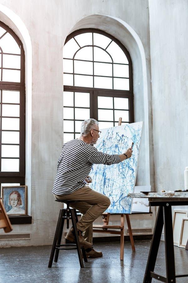 Grå färg-haired konstnärmålning på kanfas i rymligt arbetsrum arkivbild