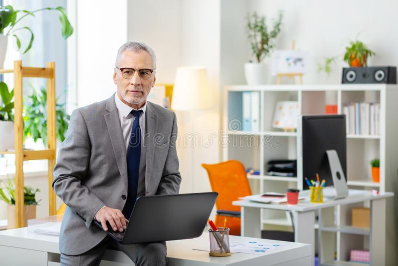 Grå färg-haired man i klara exponeringsglas som lutar på tabellen royaltyfria bilder
