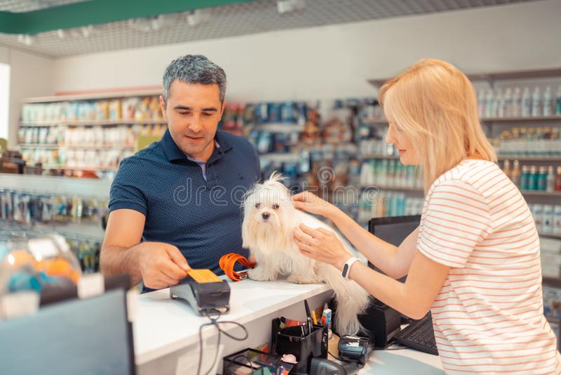 Grå färg-haired man som betalar för den vita hunden för dotter vid kortet royaltyfria foton