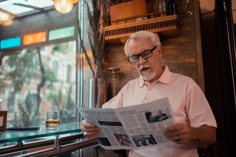 Grå färg-haired manläsningtidning som sitter i bar arkivfoto