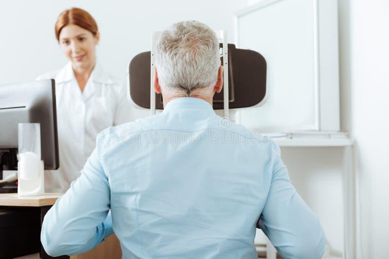 Grå färg-haired pensionerad man som har ögonsiktanalys på den privata kliniken arkivfoton