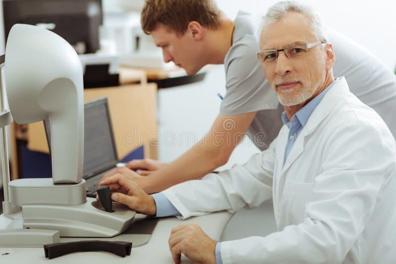 Grå färg-haired skäggig ögonläkare som sitter nära hans assistent arkivbild