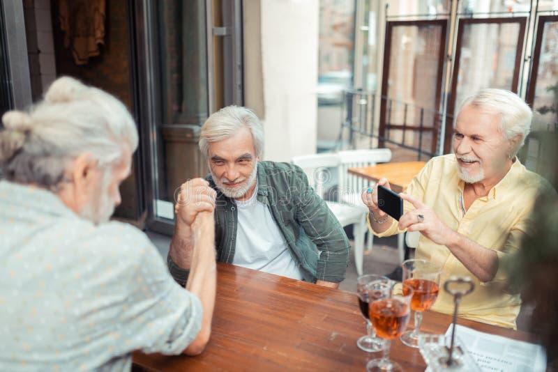 Grå färg-haired skäggig man som filmar hans vänarm-brottning arkivbild
