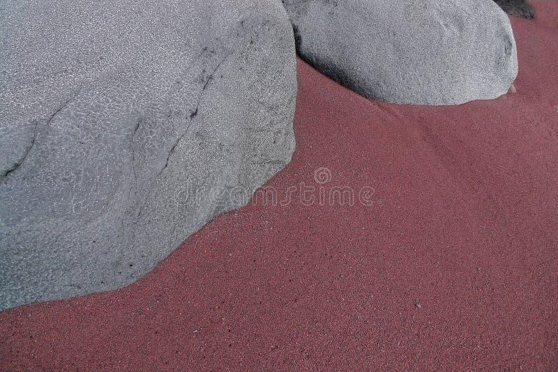 Grå färg vaggar i den rödaktiga sanden royaltyfri bild