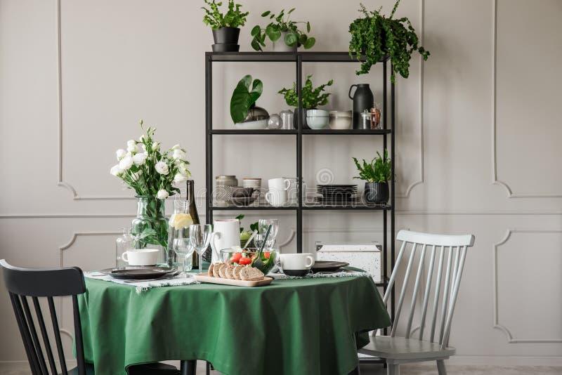Grå färgen och svarta trästolar på den runda tabellen med den gröna bordduken, plattor, rånar och vinexponeringsglas royaltyfri foto