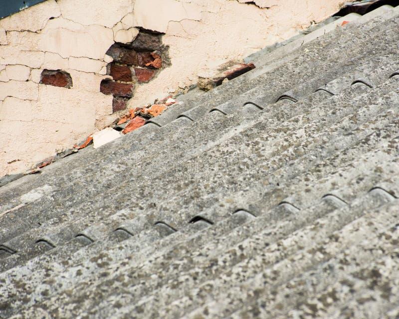 Grå färger kritiserar på taket och den spruckna väggen av huset royaltyfria foton
