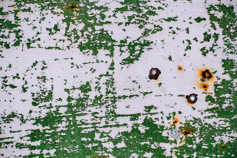 Grå färger målad metallvägg med sprucken grön målarfärg, rostfläckar, ark av rostig metall med sprucken och flagig grön målarfärg royaltyfria foton