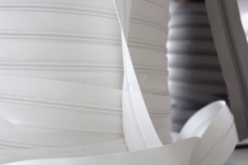 Grå färger och grå blixtlås för kläder Omfamning f?r kl?der Vit zipp i fokus fotografering för bildbyråer