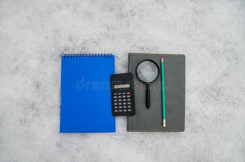 Grå färger och en blå notepad, en blyertspenna, en räknemaskin och ett förstoringsglas på en vit bakgrund arkivfoton