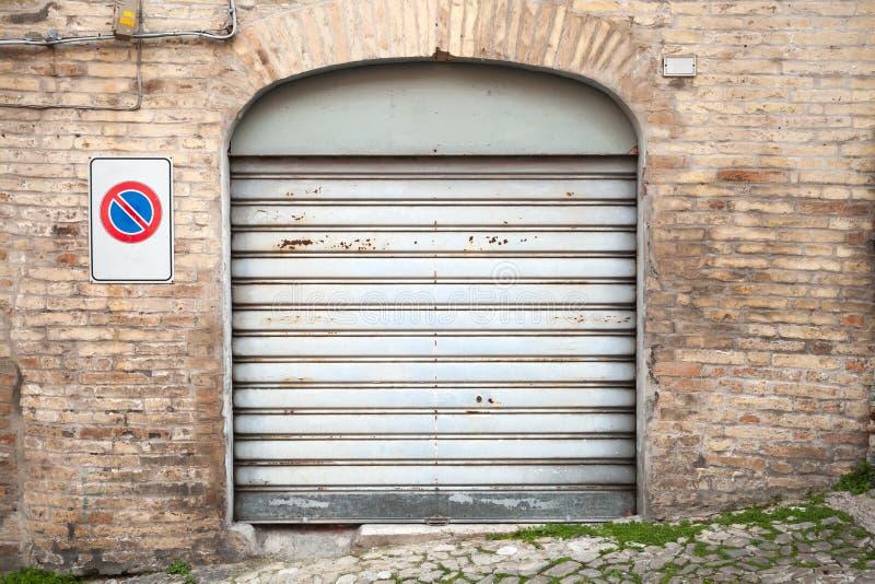 Grå färger rostad metallport i den gamla tegelstenväggen, bakgrund fotografering för bildbyråer