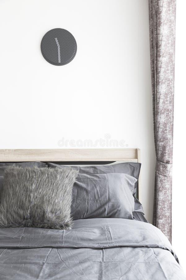 Grå färgkuddar på säng royaltyfri fotografi