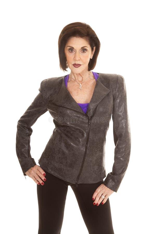 Grå färgomslag för äldre kvinna över purpurfärgade den allvarliga skjortaställningen royaltyfri bild
