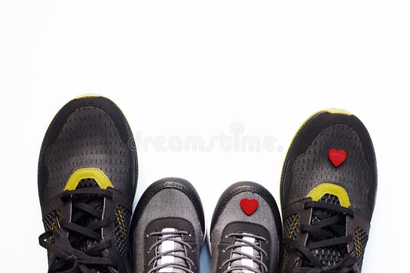 Grå färgungegymnastikskor med små röda hjärta och par av svarta vuxna gymnastikskor fotografering för bildbyråer
